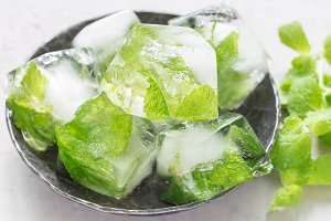 Homemade ice cubes with mint leaves inside on metal plate, fresh mint on background, ice for lemonade and cocktail, horizontal