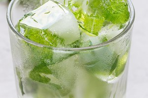 Homemade ice cubes with mint leaves inside in glass, fresh mint on background, ice for lemonade and cocktail, vertical