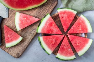 Slices of fresh seedless watermelon cut into triangle shape laying on wooden plate, flat lay, horizontal