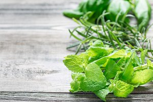 Basil, mint and rosemary. Fresh green herbs laying on wooden background, horizontal, copy space