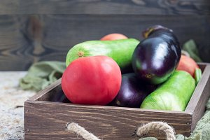 Ingredients for ratatouille or vegetable dish: eggplants, zucchini and tomato in wooden box, horizontal, copy space
