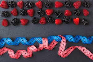 Red raspberries, blackberry and the tape measure on the black slate stone background