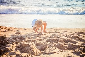 kid play with sand on summer beach