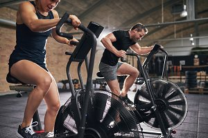 Man and woman training toughly on simulators