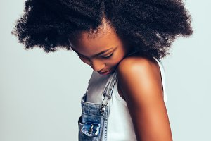 Shy young African girl standing sideways and looking down