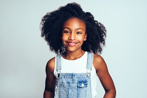 Smiling young African girl wearing dungarees against a gray background