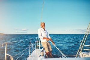 Smiling mature man out for a sail on his boat