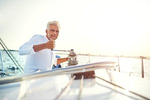 Mature man winding a winch on his sailboat