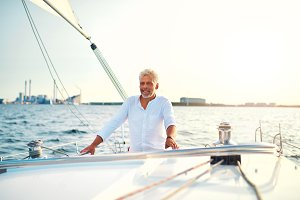 Mature man standing on the deck of his sailboat