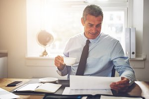 Businessman sitting at his desk reading documents and drinking coffee