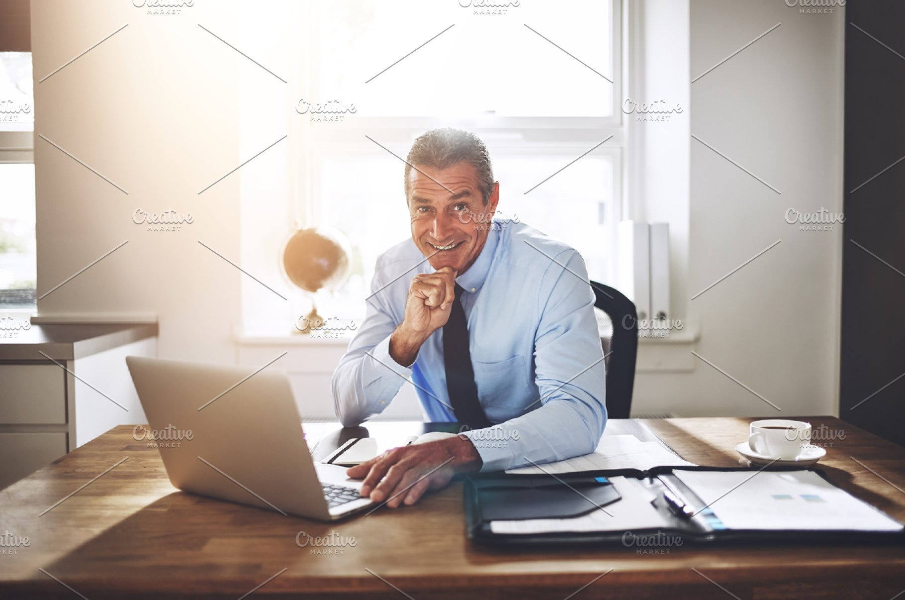 Smiling Businessman Working On A Laptop At His Office Desk