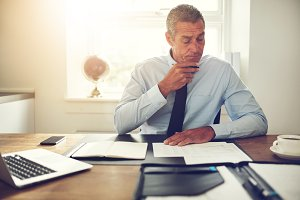 Mature businessman examining documents at his office desk
