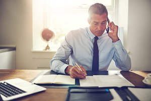 Businessman sitting at his desk discussing paperwork over the phone