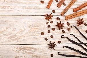 vanilla sticks, cinnamon, coffee beans and star anise on white wooden background with copy space for your text. Top view