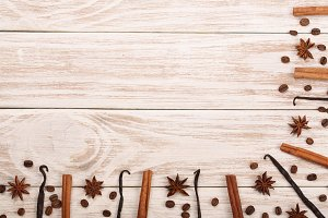 Frame of vanilla sticks, cinnamon, coffee beans on white wooden background with copy space for your text. Top view