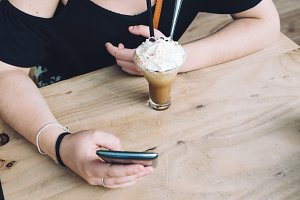 Girl drinking ice coffe and texting on her phone sitting on wood