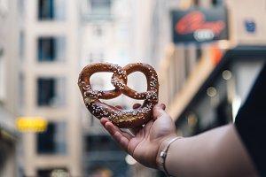 Woman hand holding a pretzel against cityscape.