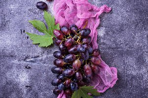 Bunch of purple grapes on concrete background