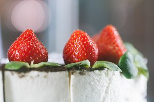 Close-up of a creamy cake with strawberries in a display case of a pastry shop.