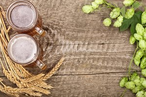 glass of foamy beer with hop cones and wheat on old wooden background. Top view with copy space for your text