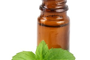 bottle of peppermint oil and fresh mint isolated on white background