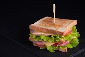 Close-up big sandwich with ham, cheese, tomatoes and salad on toasted bread on a dark background. Copy space