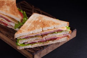 Close-up big sandwich with ham, cheese, tomatoes and salad on toasted bread on a dark background