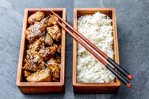 Japanese food. Chicken teriyaki with rice in wooden bento lunch box. slate background, top view.
