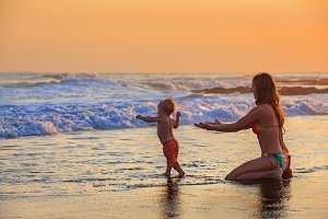 Mother with child on sunset beach