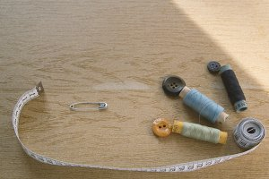 Sewing still life - multicolored cotton thread spools, thimble, needle, measuring tape