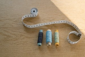 Sewing still life - different color cotton thread spools, thimble, needle, measuring tape