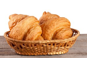 croissant in wicker basket on a wooden table with white background