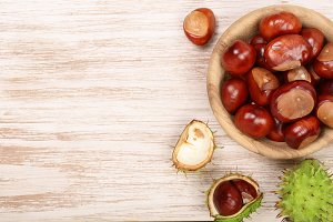 chestnut in bowl on white wooden background with copy space for your text. Top view