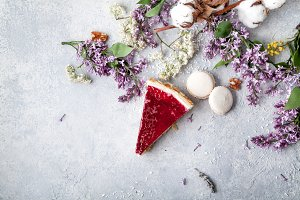 Berry cheesecake slice on concrete background with lilac flowers