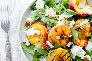 Fresh salad with grilled peach halves, arugula and burrata