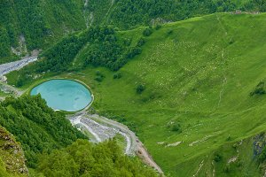 A round blue lake is in mountains