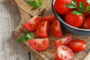 red tomatoes on a wooden board with parsley. country style