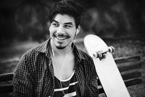 Man sitting beside skateboard