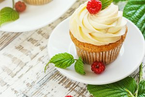 Delicate vanilla cupcakes with cream and raspberries on a white wooden background