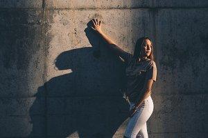 Pretty girl posing on a sunny wall