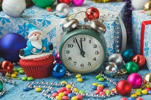 Christmas cupcake with decorative Santa made from confectionery mastic and green alarm clock