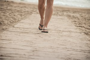 Woman walking on the beach with sand