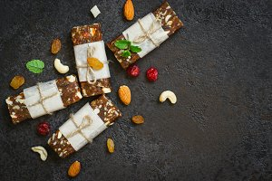 Healthy snack bars of dried fruits and nuts on black concrete background