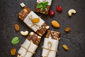 Healthy snack bars of dried fruits and nuts on black concrete ba