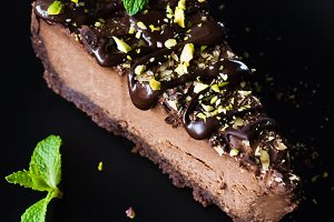 Piece of dark chocolate cream cake decorated with mint leaf