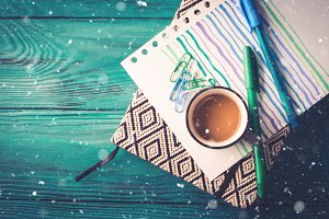 Cup of coffee, notebook and pen on dark