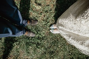 Top view of fashionable groom's and bride's legs in elegant footwear on grass. Wedding fashion and relationship concept
