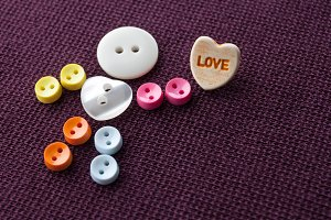 Cute funny character with love heart. Colorful sewing buttons hero on violet textile background. Valentines day concept. macro view, soft focus