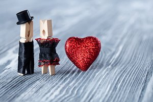 Romantic couple. Wedding invitation. Valentines day. Man, woman and read heart. Groom in black suit hat and bride in black dress. Clothespins. (Soft focus)