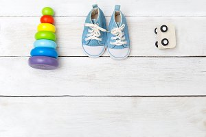 Blue baby sneakers and wooden toys.